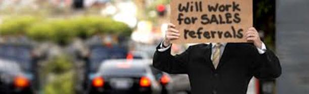 Person holding sign: Will work for sales referrals